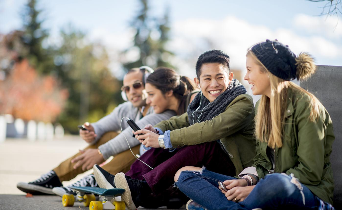 Four post-secondary education students sit in a park and laugh together.