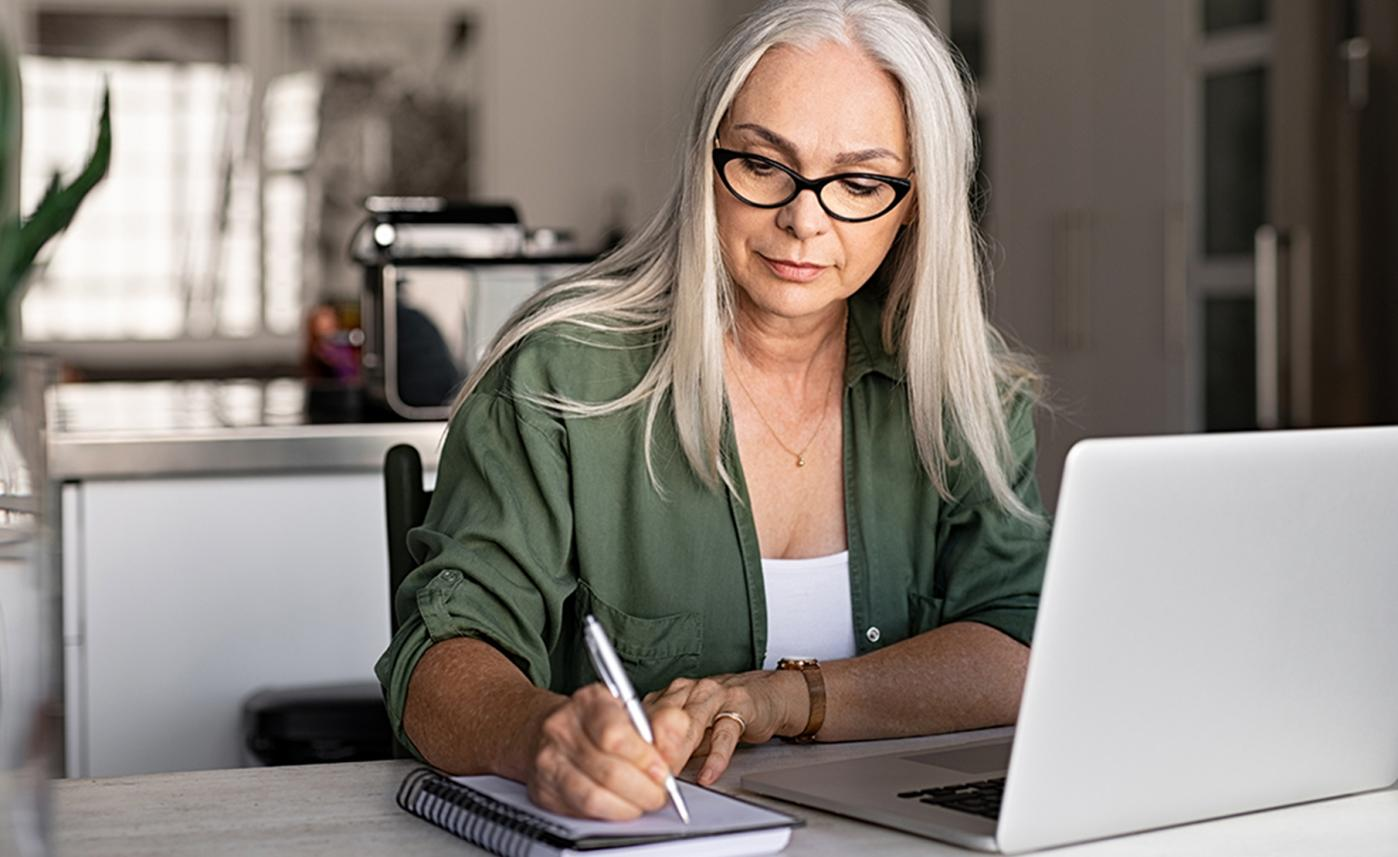 A retirement-aged woman taking notes while using her laptop.