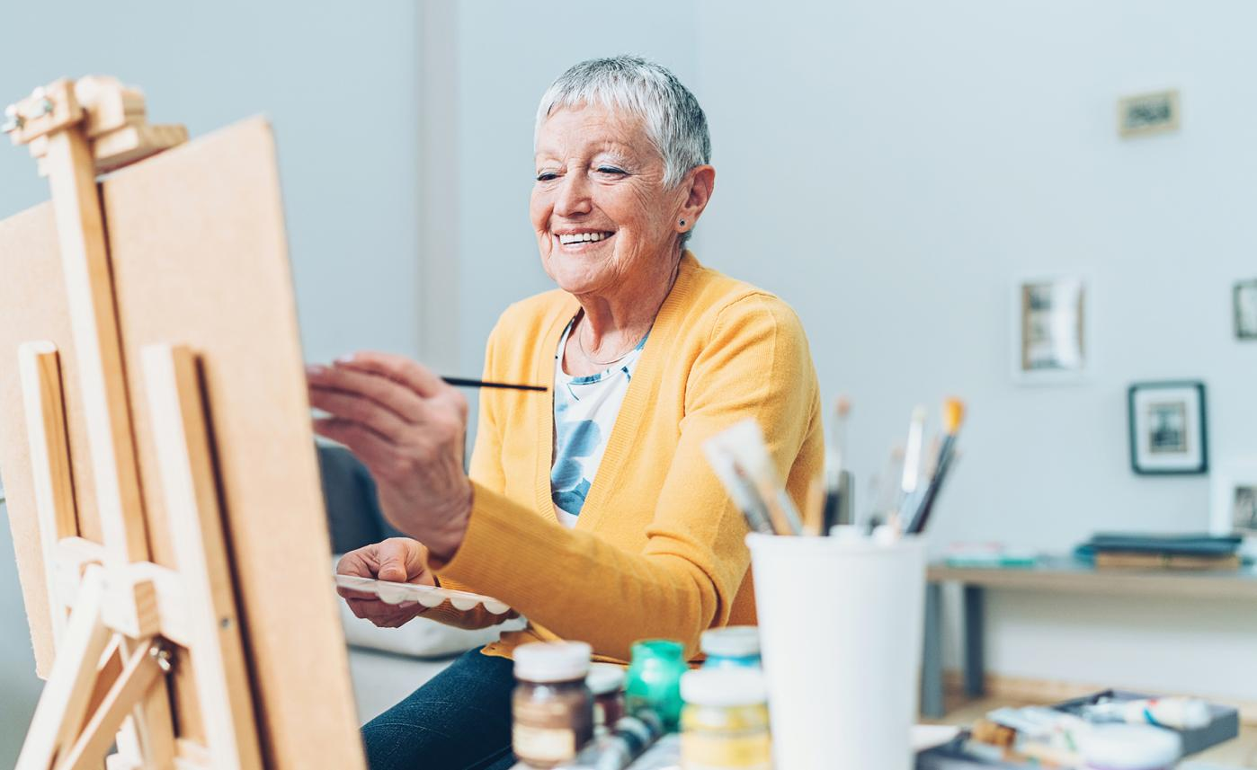 A retirement-aged woman smiles as she paints in her home studio, enjoying retirement.