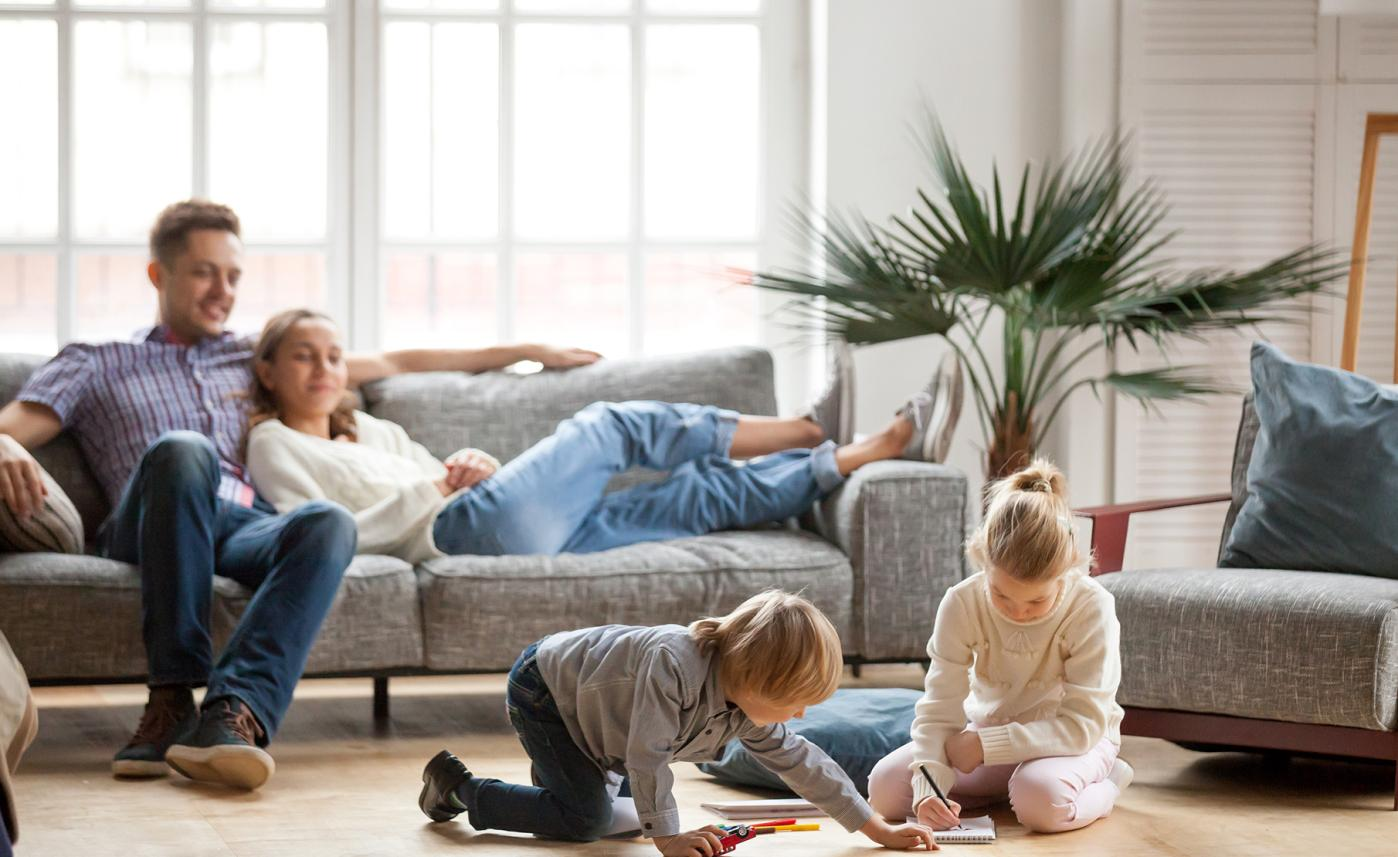 A couple sits on their couch and watches their two young children play in the living room.