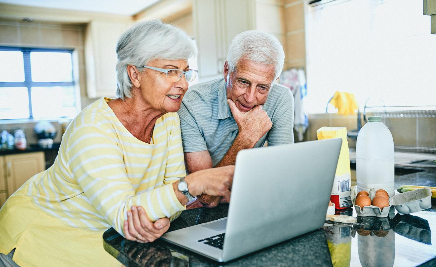 A retirement-aged couple review their finances on a laptop.