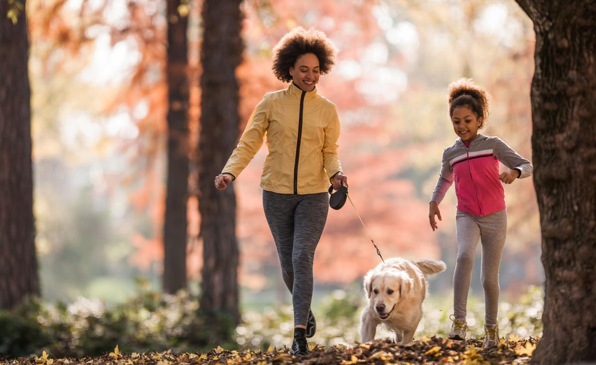 A woman with a clear vision of her financial future walks with her daughter and dog through a nature path.