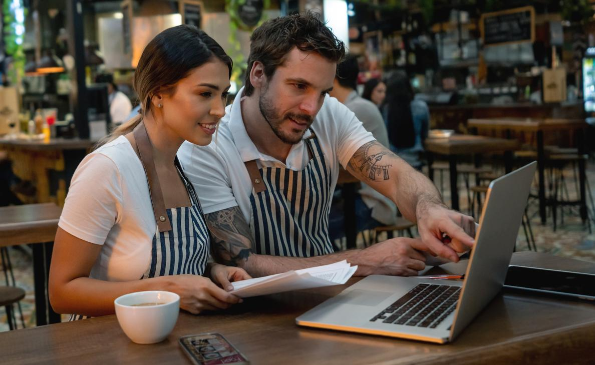 A couple of young professional small business owners reviews information on their laptop in their trendy cafe.