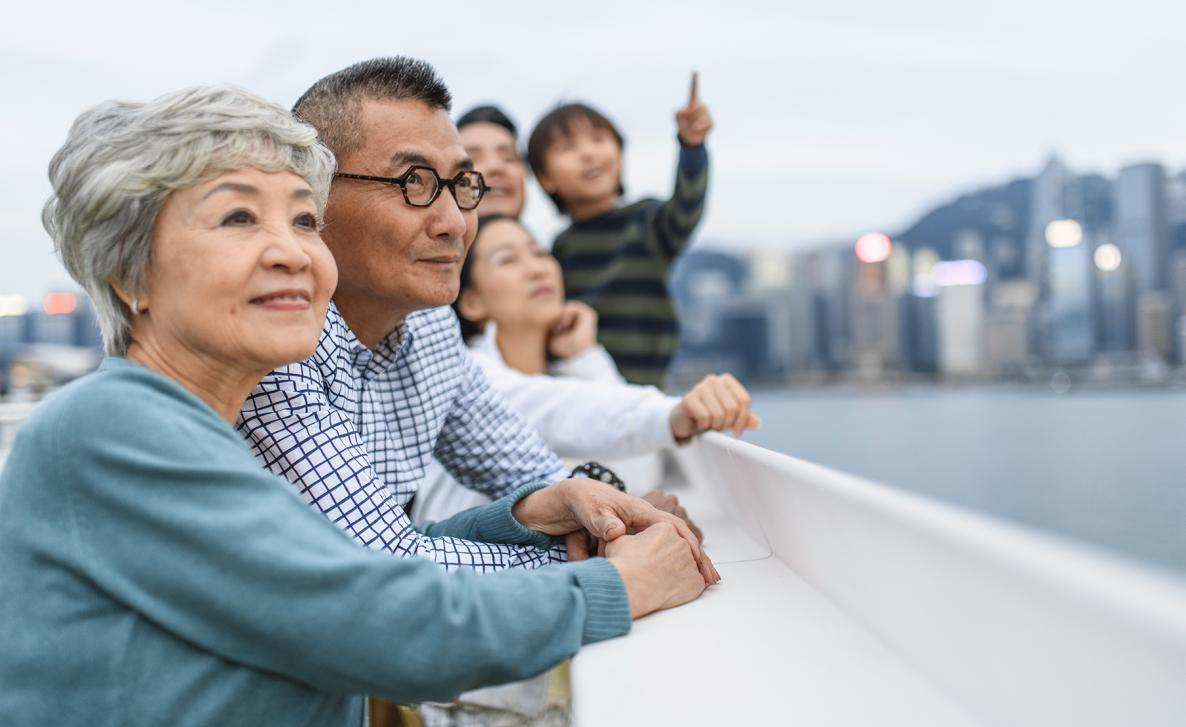 A family of three generations observes a bayside view of a metropolitan area together.