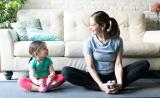 A young mother and daughter smile at one another as they do yoga together in their living room.